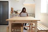 Young woman using laptop computer in her kitchen, front view