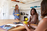 Three female friends drinking coffee together in the kitchen