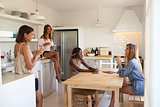 Four women drinking wine in kitchen during a girlsÕ night in