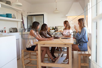 Four women at kitchen table with wine during girlsÕ night in