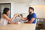 Adult couple drinking wine make a toast in the kitchen