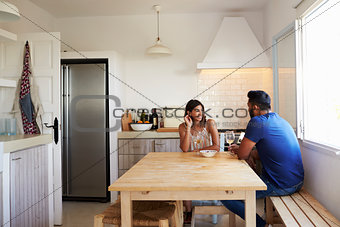 Adult couple talk and drink wine in the kitchen, copy space