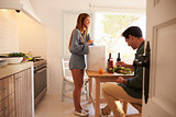 Man sitting in kitchen while his girlfriend unpacks shopping