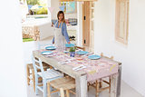 Young woman prepares table on terrace for party, full length