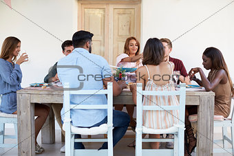 Adult friends sitting together at a dinner party on a patio