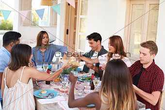 Adult friends serving each other at a patio dinner party