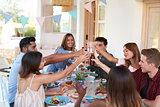 Friends making a toast at a dinner party on a patio, Ibiza