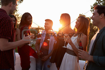 Adult friends socialising at a party on a rooftop at sunset