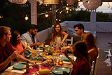 Friends talking at a dinner party on a patio, elevated view