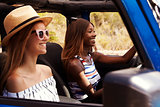 Two Female Friends Driving Open Top Car On Country Road