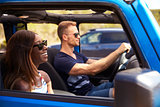 Young Couple Driving Open Top Car On Country Road
