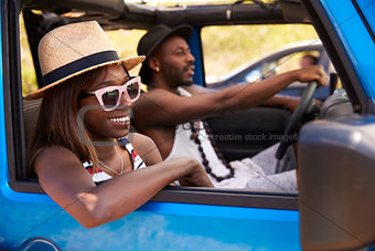 Couple Driving Open Top Car On Country Road