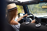 Young Woman Driving Open Top Car On Country Road