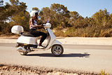 Young Woman Riding Motor Scooter On Country Road