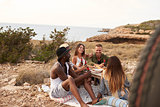 Group Of Friends Enjoying Picnic On Cliffs By Sea