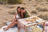Couple Enjoying Picnic On Cliffs By Sea