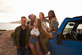 Portrait Of Friends Standing By Open Top Car On Cliffs