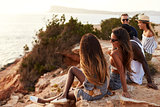 Rear View Of Friends Sitting On Cliff Watching Sunset