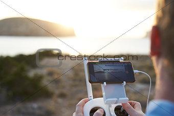 Close Up Of Man Flying Drone Over Coastal Landscape