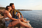 Side View Of Couple Sitting On Cliff Watching Sunset