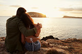 Rear View Of Couple Sitting On Cliff Watching Sunset