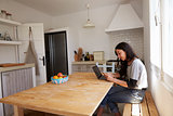 Smiling girl with laptop, reading message on phone in kitchen