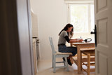 View from doorway of teenage girl doing homework in kitchen