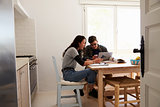 Two teenagers with laptop using smartphones at kitchen table