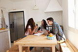Teenage girl showing smartphone to her friends in a kitchen