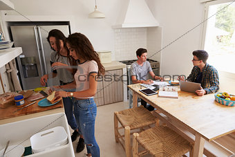 Four teenagers making lunch and studying together in kitchen