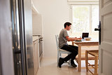 View from doorway of teenage boy studying in a kitchen