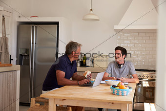 Dad and son using technology eat and talk at kitchen table