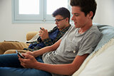 Two teenage boys relax, messaging friends with smartphones
