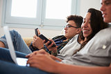 Teenage friends relax watching laptop and smartphone at home