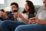 Three teenagers sitting together using smartphones at home