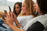 Three teenage girls using smartphones at home, close up