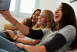 Teenage girl taking selfie with friends using her smartphone