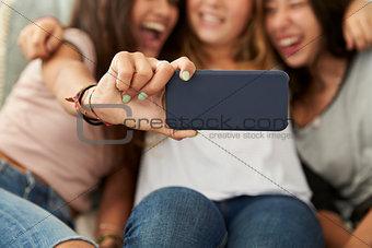 Three teenage girls taking selfie at home, focus on phone