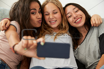 Three teenage girls taking selfie at home, focus on girls