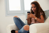 Teenage girl text messaging with smartphone at home