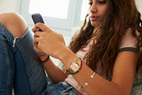 Teenage girl text messaging with phone at home, close up