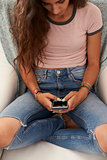 Teenage girl using smartphone at home, elevated view