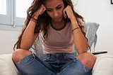 Teenage girl sits cross legged at home thinking, tight crop