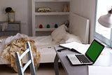 TeenagerÕs bedroom, with laptop on desk and unmade bed