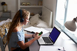 Girl wearing headphones using smartphone at desk in bedroom