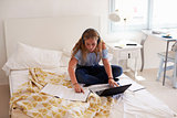 Teenage girl reading homework sitting on her bed with laptop