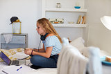 Girl text messaging sits with homework and laptop on her bed