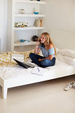 Girl on phone, with homework and laptop on her bed, vertical