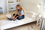 Girl using laptop for homework sitting cross legged on bed