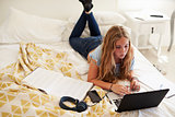 Teenage girl lying on bed working with laptop, high angle